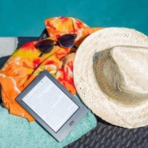 Summer hat, sunglasses, beach towel, and tablet computer