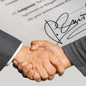 Shaking hands over a signed contract