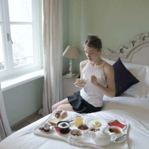 A woman seated on a bed sampling foods