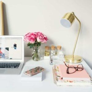 colorful desk with laptop and journals
